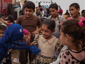 Grover (Sesame Street) with refugee children in Jordan